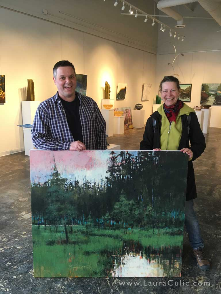 Artists Shane Norrie (L) and Laura Culic (R) with her painting in his gallery